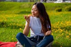 Hembra joven con la rebanada larga de la tenencia del pelo de pizza mientras que se sienta en hierba y disfruta del almuerzo fotografía de archivo