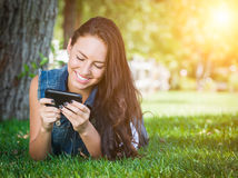 Hembra joven de la raza mixta que manda un SMS en el teléfono celular afuera en el Gra Fotografía de archivo libre de regalías