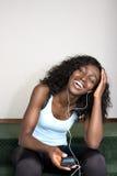 Hembra joven del afroamericano que escucha la música Foto de archivo