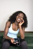 Hembra joven del afroamericano que escucha la música imagenes de archivo