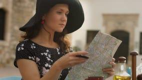 Hembra joven elegante en viaje del planeamiento del café en el extranjero, estudiando el mapa, comprobando las rutas almacen de video