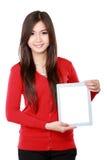 Hembra joven en el rojo que muestra la tableta en blanco Fotografía de archivo