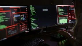 Hembra joven en los datos de entrada oscuros, códigos de ordenador, rompiendo el sistema de seguridad