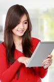 Hembra joven en rojo usando la tableta Fotos de archivo libres de regalías