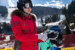 Hembra joven en traje de esquí, con el casco y las gafas del esquí poniendo Imagen de archivo libre de regalías