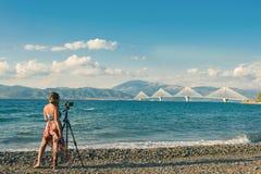 """Hembra joven en un vestido en la playa con el trípode y cámara que toma la imagen del """"de Ñ del puente de Rion-Antirion Patras Gr Foto de archivo libre de regalías"""