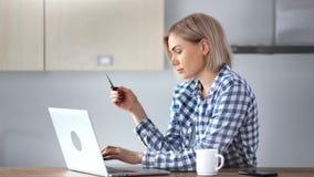 Hembra joven enfocada que disfruta de las compras en línea que hacen paga usando el primer medio de la tarjeta de crédito almacen de video
