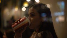 Hembra joven feliz que goza del café en café, mirando en ventana y la sonrisa almacen de video