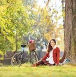 Hembra joven hermosa con la bicicleta que se sienta en parque y la mirada Imagen de archivo libre de regalías