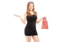 Hembra joven hermosa en el vestido negro que sostiene un bolso y un gesturin Imagen de archivo libre de regalías