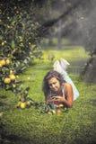 Hembra joven hermosa en guardapolvos en el manzanar Fotografía de archivo