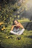 Hembra joven hermosa en guardapolvos en el manzanar Imagen de archivo