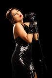 Hembra joven hermosa en vestido negro que canta Imagenes de archivo