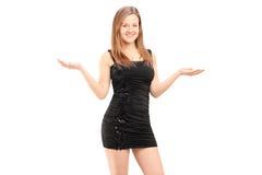 Hembra joven hermosa en vestido negro que gesticula con sus manos Fotos de archivo