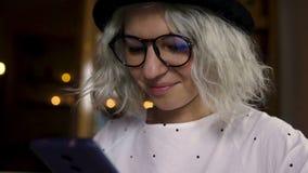 Hembra joven hermosa que usa smartphone almacen de metraje de vídeo