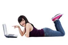 Hembra joven linda que miente en suelo con la computadora portátil Foto de archivo