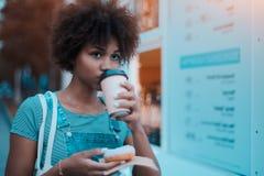 Hembra joven negra con el buñuelo y el café al aire libre Fotografía de archivo