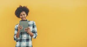 Hembra joven negra del estudiante con la tableta digital Foto de archivo