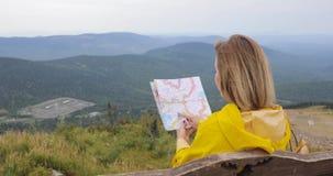 Hembra joven que camina el impermeable amarillo im con una mochila en las montañas que sostienen el mapa de papel en manos metrajes