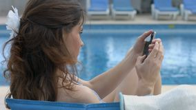 Hembra joven que charla en línea en smartphone, teniendo resto del verano almacen de video