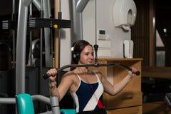 Hembra joven que hace ejercicios traseros en el gimnasio Foto de archivo libre de regalías