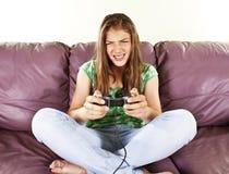 Hembra joven que juega juegos de video Imágenes de archivo libres de regalías