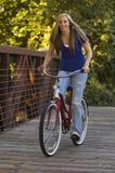 Hembra joven que monta una bici Fotos de archivo