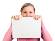 Hembra joven que muestra una tarjeta blanca Fotografía de archivo libre de regalías