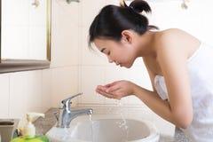 Hembra joven que se lava la cara en cuarto de baño Imagen de archivo libre de regalías