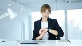 Hembra joven que usa el smartwatch en el trabajo en oficina metrajes
