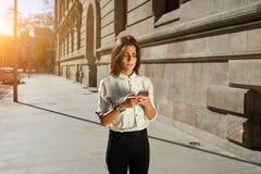 Hembra joven que usa el teléfono móvil mientras que da un paseo en la ciudad Foto de archivo libre de regalías