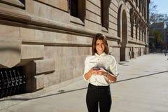 Hembra joven que usa el teléfono móvil mientras que da un paseo en la ciudad Imagenes de archivo