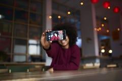 Hembra joven que usa el uso y la conexión inalámbrica a Internet en espacio coworking durante tiempo libre Foto de archivo libre de regalías