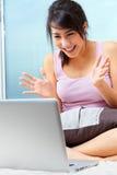 Hembra joven que usa la computadora portátil Foto de archivo libre de regalías