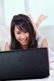 Hembra joven que usa la computadora portátil Imágenes de archivo libres de regalías