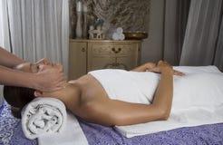 Hembra joven relajada que consigue un masaje de piedra en un balneario Imágenes de archivo libres de regalías