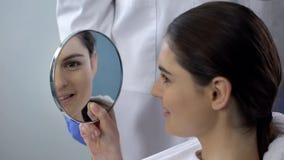 Hembra joven satisfecha con resultado de la rinoplastia, cara sonriente reflejada en espejo foto de archivo libre de regalías