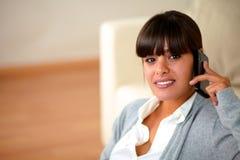 Hembra joven sonriente que conversa en el teléfono móvil Imagen de archivo libre de regalías