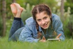Hembra joven sonriente que usa la tableta digital mientras que miente en al aire libre Fotografía de archivo