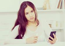 Hembra joven trastornada con el teléfono móvil Fotografía de archivo libre de regalías