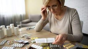 Hembra jubilada en vidrios que lee la instrucción de la medicina, industria farmacéutica imagen de archivo libre de regalías