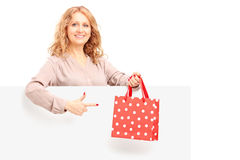 Hembra madura que sostiene un bolso y que gesticula en un panel en blanco Foto de archivo libre de regalías