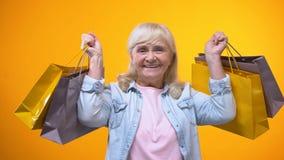 Hembra mayor alegre que sostiene los bolsos de compras, tiempo libre agradable, anuncio almacen de metraje de vídeo