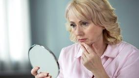 Hembra mayor infeliz que mira la cara de la piel que cede en el espejo, aspecto de la edad avanzada imagen de archivo
