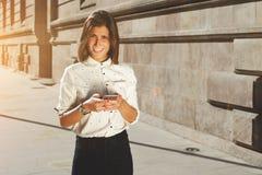 Hembra morena atractiva que usa el teléfono móvil con el área de espacio de la copia para su mensaje de texto o contenido promoci Foto de archivo