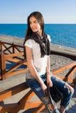 Hembra morena joven del pelo en ropa de moda que disfruta de tarde soleada hermosa mientras que se sienta en la playa contra el m Fotografía de archivo
