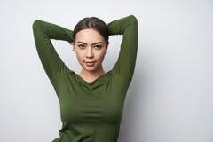 46c17f208 Hembra morena sonriente en la situación verde de la camisa con las manos  por encima imagen