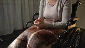 Hembra nerviosa discapacitada que aprieta las manos, sintiendo solo y desamparado, silla de ruedas almacen de metraje de vídeo