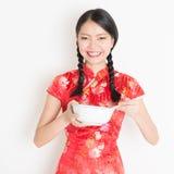 Hembra oriental en cheongsam rojo que come con los palillos Imagen de archivo libre de regalías