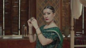 Hembra preciosa en la sari hindú que toca los platillos del choque